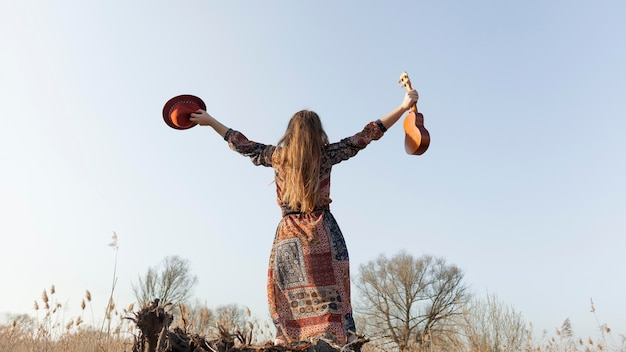Vista traseira, de, boêmio, mulher segura, teve, e, ukulele Foto gratuita