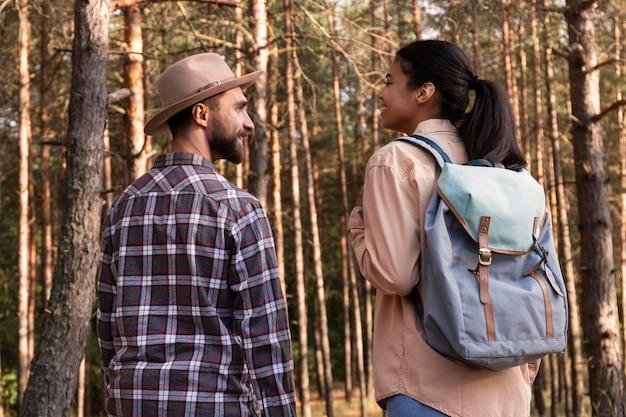 Vista traseira de casal dando um passeio na floresta Foto gratuita