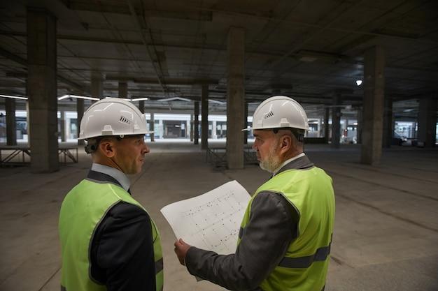 Vista traseira de dois empresários usando capacetes e segurando planos enquanto estavam no canteiro de obras, Foto Premium
