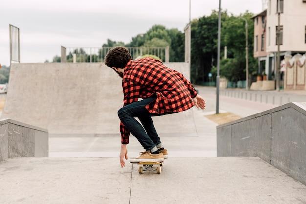 Vista traseira, de, homem, em, parque patim Foto gratuita