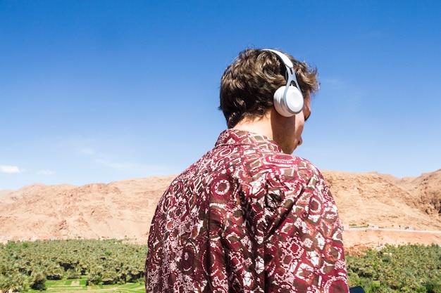 Vista traseira, de, homem, escutar música, em, oásis Foto gratuita