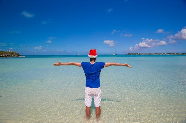 Vista traseira, de, homem jovem, em, chapéu santa, ligado, praia tropical Foto Premium