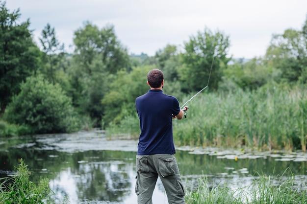 Vista traseira, de, homem jovem, pesca, em, a, lago Foto gratuita