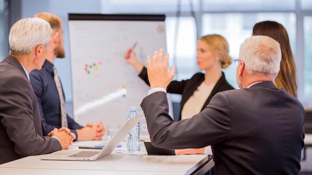 Vista traseira, de, homem negócios sênior, fazendo perguntas, durante, apresentação Foto gratuita