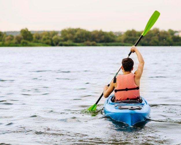 Vista traseira, de, homem, remar, caiaque, ligado, idyllic, lago Foto gratuita
