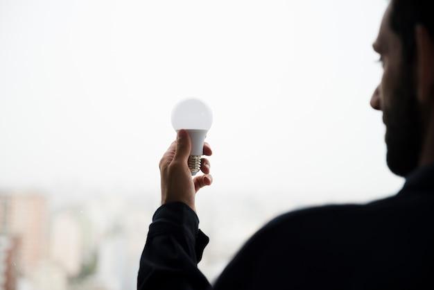 Vista traseira, de, homem, segurando, branca, bulbo elétrico Foto gratuita