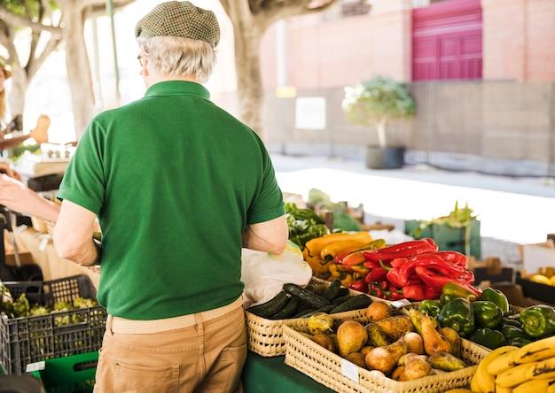 Vista traseira, de, homem sênior, ficar, em, vegetal, e, fruta, tenda Foto gratuita