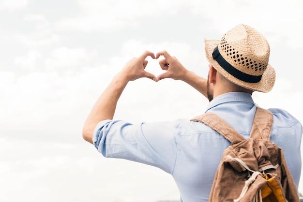 Vista traseira, de, homem viajante, fazer, forma coração, de, dedo, contra, céu nublado Foto gratuita