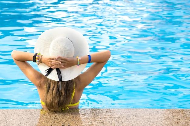 Vista traseira de jovem mulher com cabelo comprido, usando chapéu de palha amarelo relaxante na piscina quente de verão com água azul em um dia ensolarado. Foto Premium