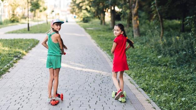 Vista traseira, de, meninas, montando, pontapé scooter, ligado, pavimento, parque Foto gratuita