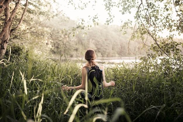 Vista traseira, de, mulher caminhando, em, grama verde, perto, a, lago Foto gratuita