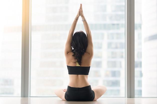 Vista traseira, de, mulher jovem, sentando, em, ardha padmasana, pose Foto gratuita