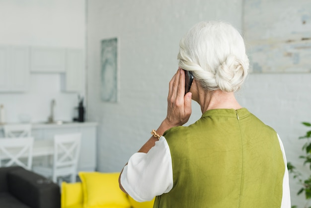 Vista traseira, de, mulher sênior, conversa num smartphone, casa Foto gratuita
