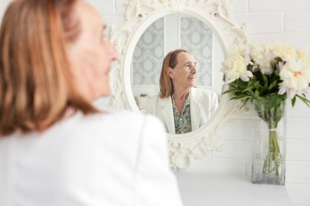 Vista traseira, de, mulher sênior, sentando, frente, espelho, olhando Foto gratuita