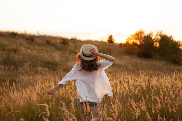 Vista traseira de mulher usando chapéu e posando no campo Foto gratuita