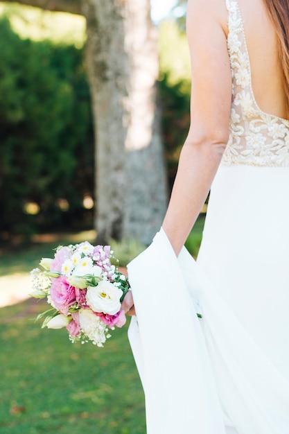 Vista traseira, de, noiva, mão, segurando, bonito, buquê flor Foto gratuita