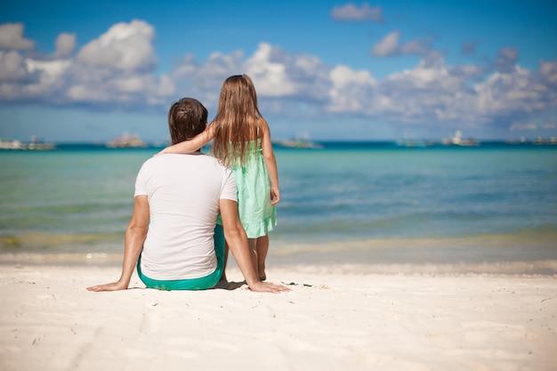 Vista traseira, de, pai jovem, e, seu, filha pequena, olhe mar Foto Premium