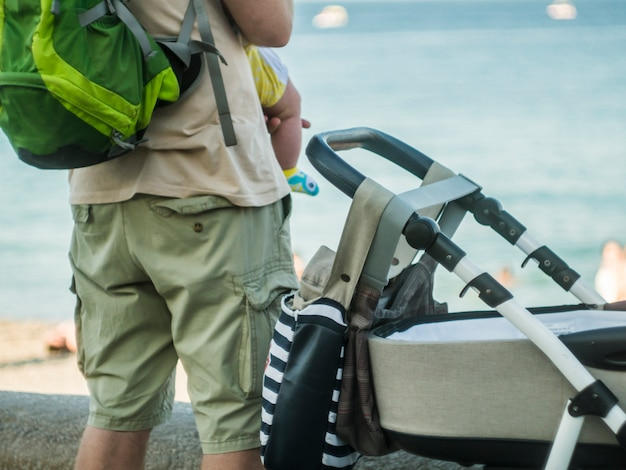 Vista traseira, de, pai, segurando, criança bebê, em, braços, ficar, perto, a, storoller, andar, ao ar livre, conceito familiar Foto Premium