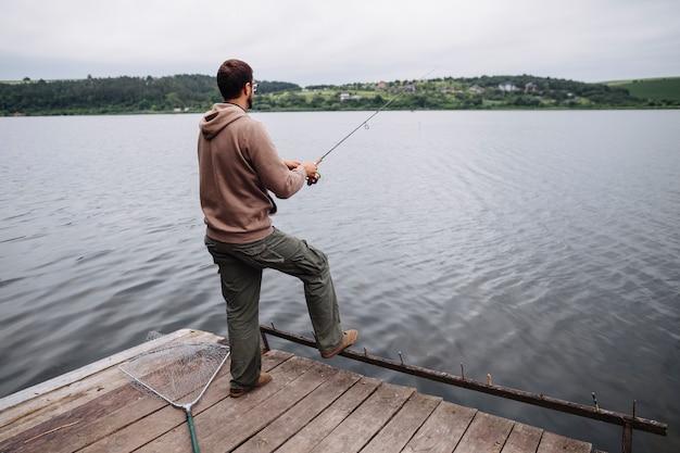 Vista traseira, de, posição homem, ligado, cais, pesca, em, a, lago Foto gratuita