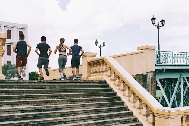 Vista traseira de quatro pessoas no sportswear correndo no andar de cima no centro da cidade Foto gratuita