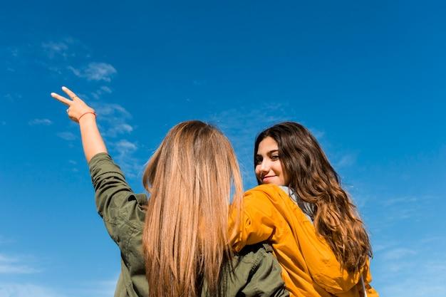 Vista traseira, de, sorrindo, menina jovem, com, dela, amigo, gesticule, sinal vitória Foto gratuita