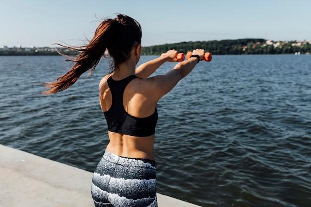 Vista traseira, de, treinamento mulher, com, pesos Foto gratuita