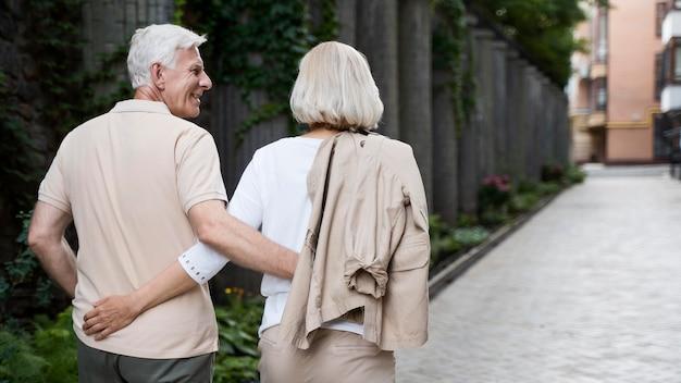 Vista traseira de um casal de idosos abraçado caminhando ao ar livre Foto gratuita