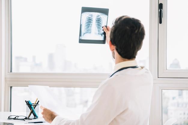 Vista traseira, de, um, doutor masculino, examinando, radiografia tórax Foto gratuita