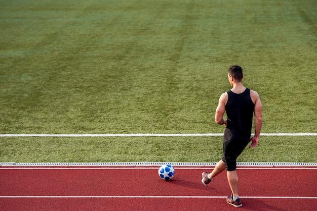 Vista traseira de um esportista jogando na pista de corrida com bola de futebol Foto gratuita