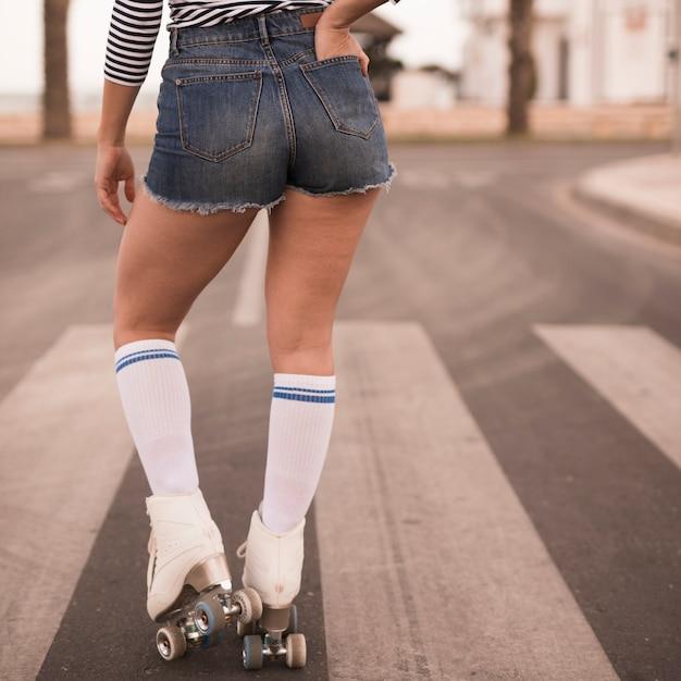 Vista traseira, de, um, femininas, patinador, com, dela, mão, em, bolso, ficar, ligado, estrada Foto gratuita