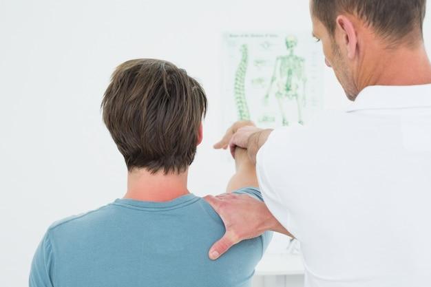Vista traseira, de, um, fisioterapeuta, esticar, um, homens, braço Foto Premium