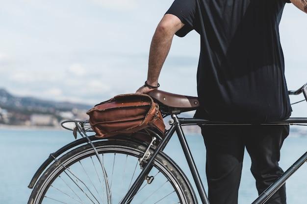Vista traseira, de, um, homem, inclinar-se, bicicleta, perto, a, costa Foto gratuita