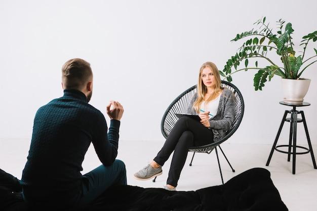 Vista traseira, de, um, homem jovem, discutir, dela, problemas, com, femininas, psicólogo, sentar-se cadeira, em, escritório Foto Premium