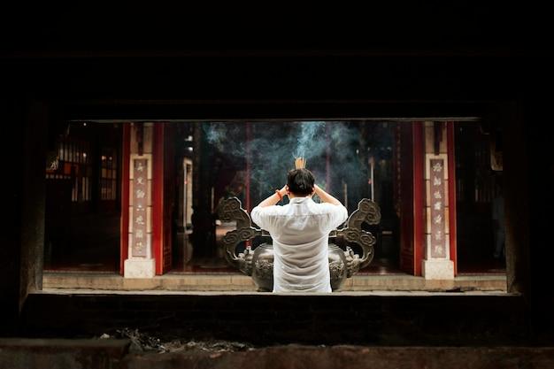 Vista traseira de um homem orando no templo com incenso queimando Foto gratuita
