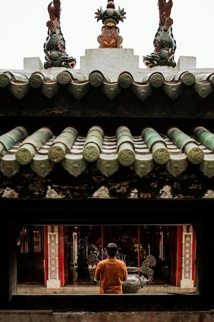 Vista traseira de um homem orando no templo com incenso Foto gratuita