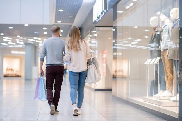 Vista traseira de um jovem casal casual se movendo ao longo da vitrine de uma loja no shopping enquanto a deixa após comprar o que quer Foto Premium