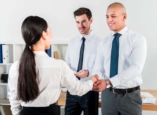 Vista traseira, de, um, jovem, executiva, apertar mão, com, homem negócios Foto gratuita