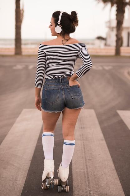 Vista traseira, de, um, jovem, femininas, patinador, com, dela, mãos, em, bolso, escutar, música, ligado, headphone, olhar ombro Foto gratuita