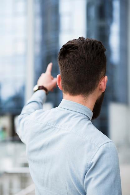 Vista traseira, de, um, jovem, homem negócios, apontar, dedo Foto gratuita