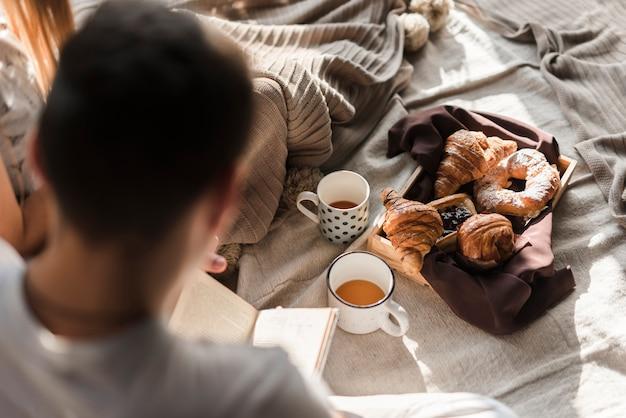 Vista traseira, de, um, leitura homem, livro, com, café manhã cama Foto gratuita