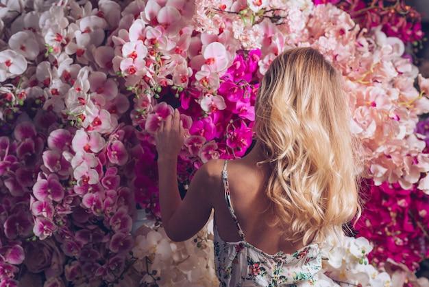 Vista traseira, de, um, loiro, mulher jovem, olhar, orquídea, flores Foto gratuita