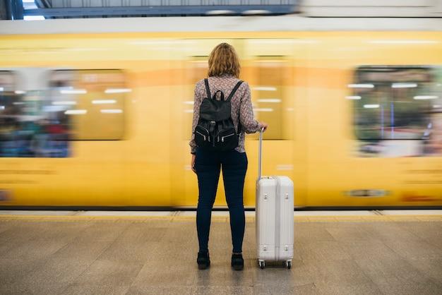 Vista traseira, de, um, loura, mulher espera, em, a, trem, plataforma Foto gratuita