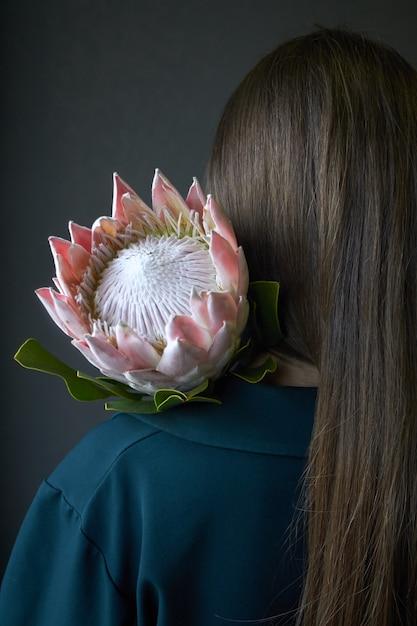 Vista traseira, de, um, menina, com, cabelo escuro, segurando, um, rosa protea, flor, ligado, um, fundo escuro, foco seletivo Foto Premium
