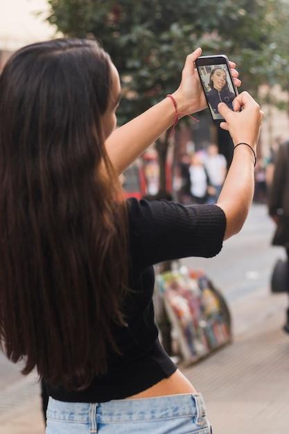 Vista traseira, de, um, mulher jovem, levando, selfie, ligado, telefone móvel, em, rua Foto gratuita