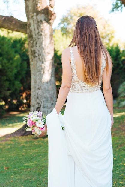 Vista traseira, de, um, noiva, ficar, parque, segurando, buquê flor, em, mão Foto gratuita