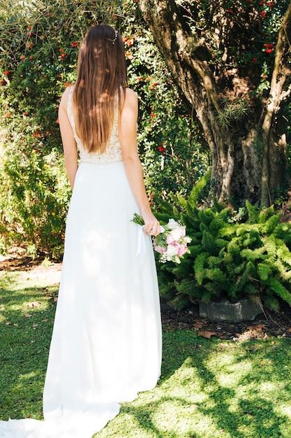 Vista traseira, de, um, noiva, segurando, buquê flor, em, mão, ficar, parque Foto gratuita