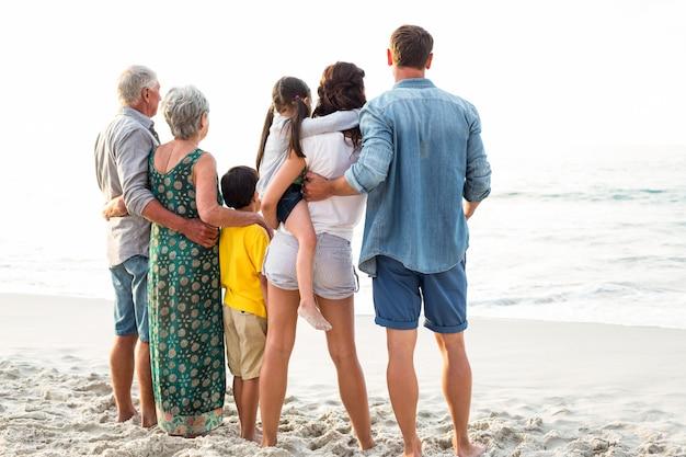 Vista traseira de uma família feliz posando na praia Foto Premium