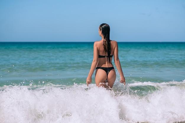 Vista traseira de uma jovem bonita fitness biquíni preto sexy com espólio desportivo em pé na água do mar. conceito de férias. férias de verão. turismo. Foto Premium