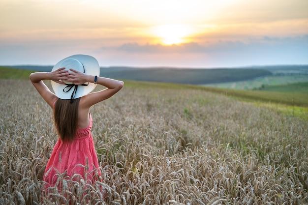 Vista traseira de uma jovem mulher feliz com vestido vermelho de verão e pé de chapéu de palha no prado amarelo da fazenda com trigo dourado maduro, levantando as mãos, apreciando a noite quente. Foto Premium