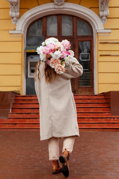 Vista traseira de uma linda mulher segurando um buquê de flores do lado de fora Foto gratuita